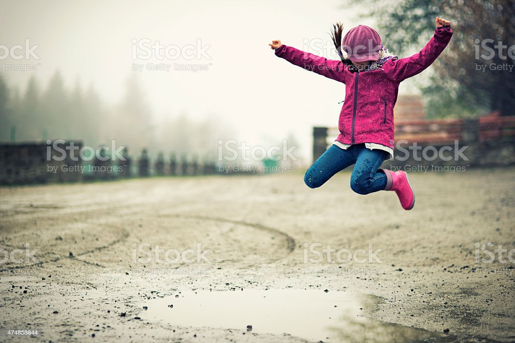 Little girl jumping into puddle stock photo