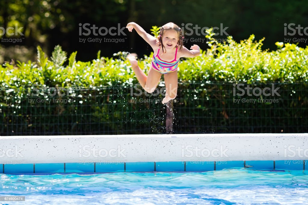 Little girl jumping into swimming pool royalty-free stock photo