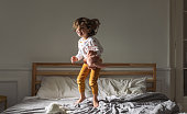 Adorable happy little girl in pajamas jumping on king-size bed in the morning.