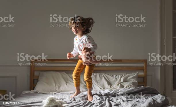 Little girl jumping on a bed picture id1187599099?b=1&k=6&m=1187599099&s=612x612&h=7ib6ccw7cn q1fqxpmkspk3qbjfvd5yoar2lx7jjqba=