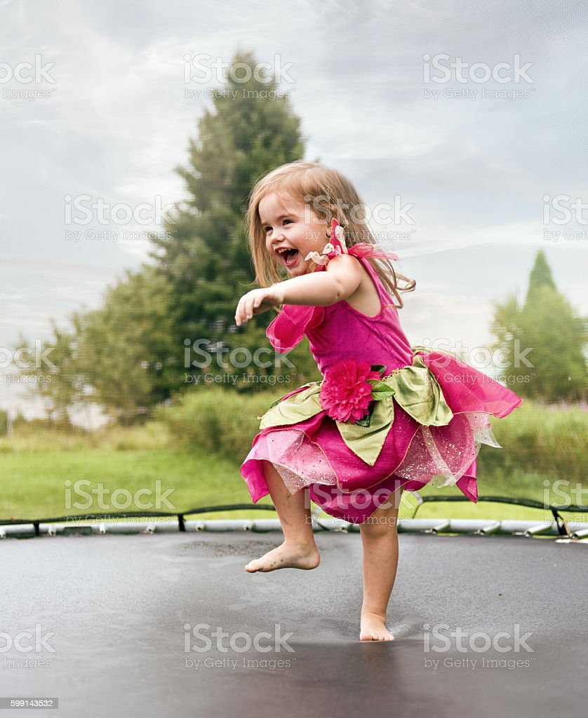 Little girl jumping on a trampoline stock photo