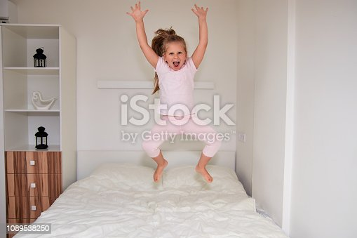 istock Little girl jumping on bed at home 1089538250