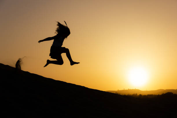 Little girl jumping over sand dunes on sunset in Maspalomas, Gran Canaria stock photo