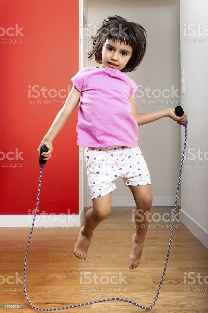 Little girl jumping rope at home royalty-free stock photo