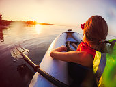 Little girl is kayaking together with her father at sunset. Real people, genuine scene.