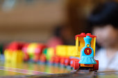 Little girl kid playing with plastic train toy