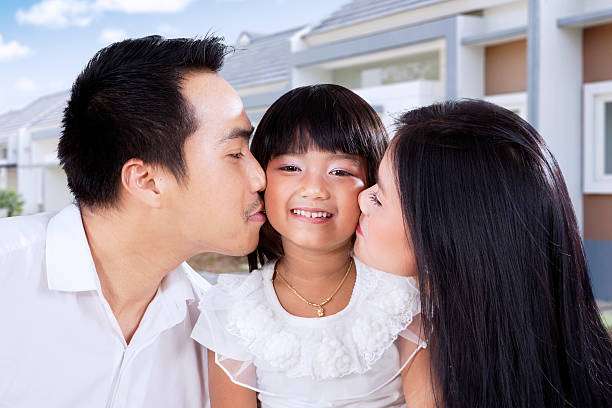 Little girl kissed by her parents Portrait of a cheerful little girl kissed by her parents in front of their new house little girl kissing dad on cheek stock pictures, royalty-free photos & images