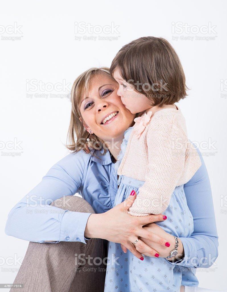 Little girl kisses her mother stock photo