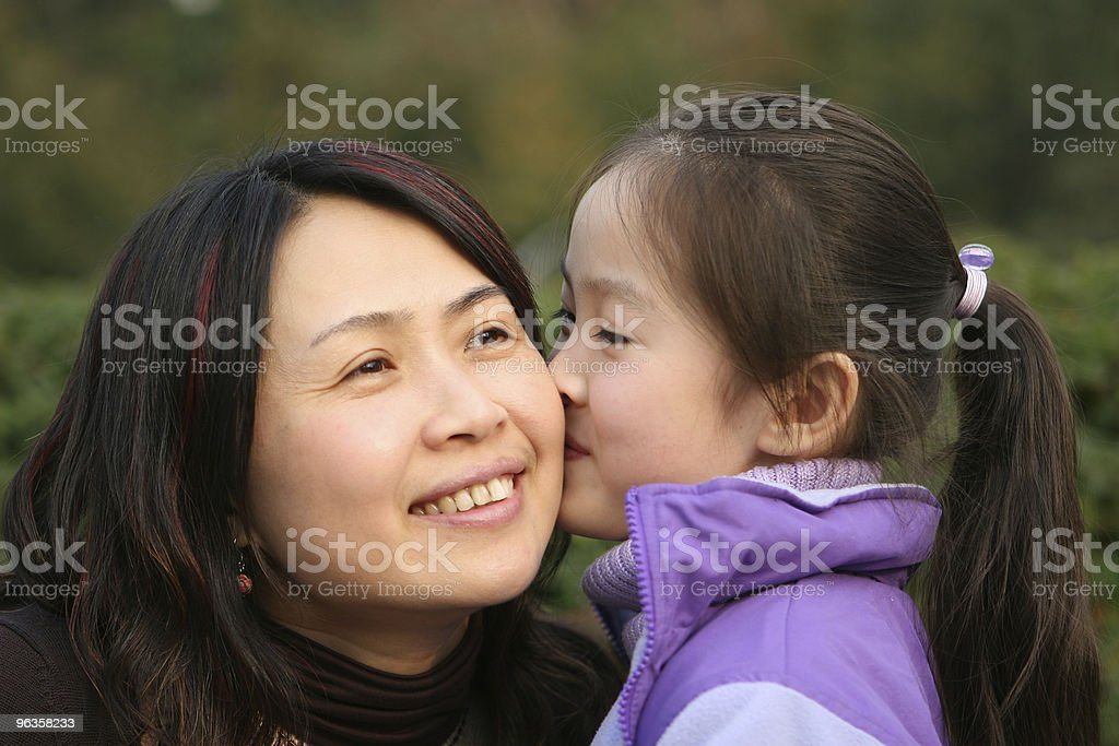 little girl kisses her mother royalty-free stock photo
