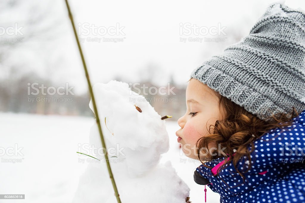 Little girl kissing a snowman in winter nature - foto de acervo