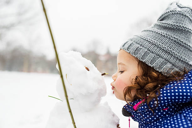 Little girl kissing a snowman in winter nature stock photo