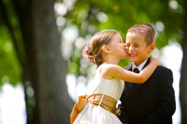 little girl kissing boy at wedding - little girls little boys kissing love stock photos and pictures