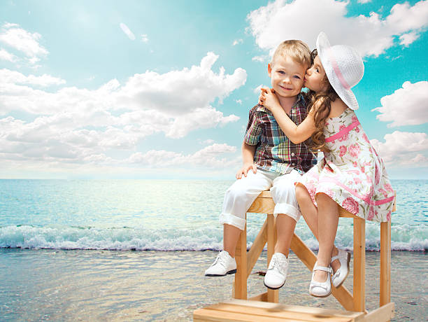 little girl kissing boy on sea landscape at sunset - little girls little boys kissing love stock photos and pictures