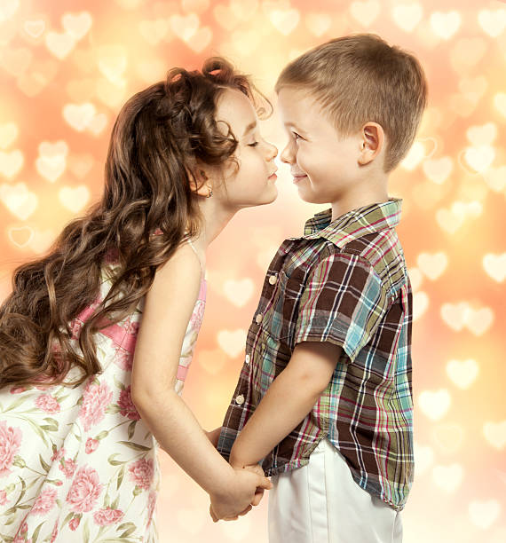 little girl kissing boy - little girls little boys kissing love stock photos and pictures