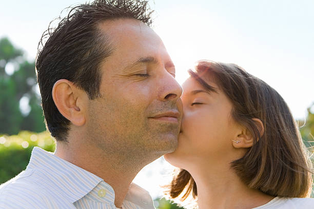Little Girl Kissing Dad on Cheek A Special Father Daughter Moment of Affection little girl kissing dad on cheek stock pictures, royalty-free photos & images