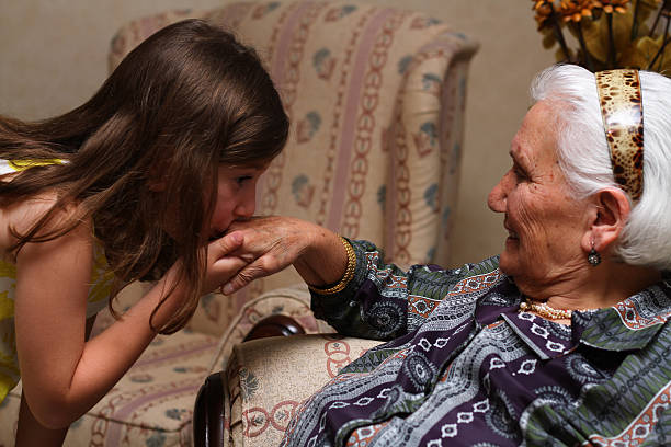 little girl kissing Grandmather hand at religious festival little girl kissing Grandmather hand at religious festival kissinghand stock pictures, royalty-free photos & images