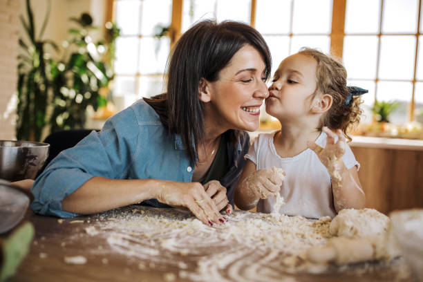 Little girl kissing her mom in the kitchen stock photo