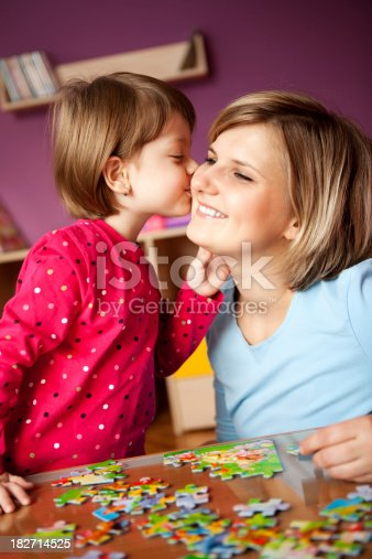 istock Little girl kissing her mother while playing with puzzle 182714525
