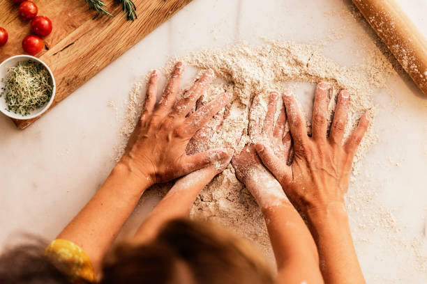 Little girl kneading flour with her mother. stock photo