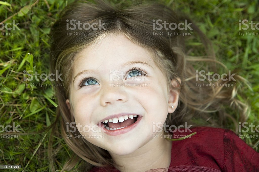 Little girl laughing and lying on grass. royalty-free stock photo