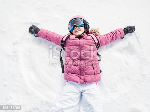 Little girl playing snow angel