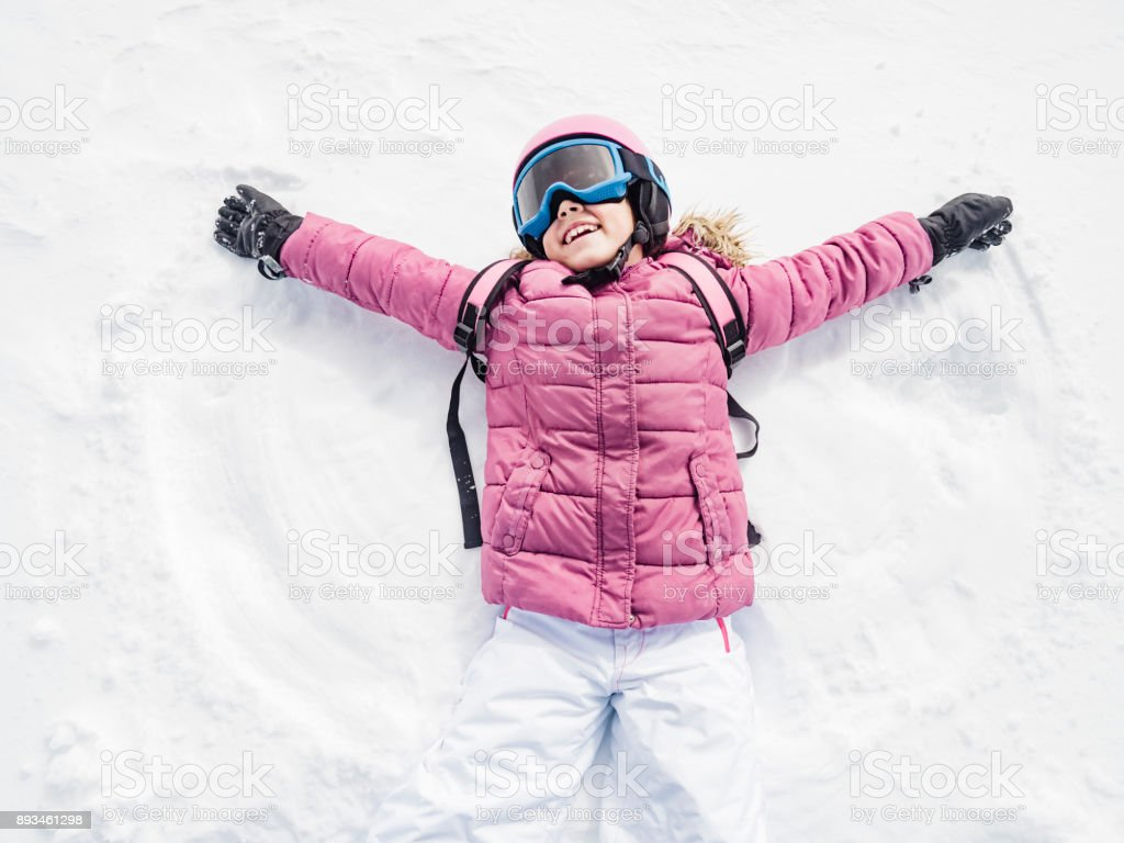 Little girl laughing and playing snow angel stock photo