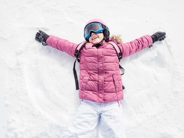 little girl laughing and playing snow angel - aluxum stock pictures, royalty-free photos & images