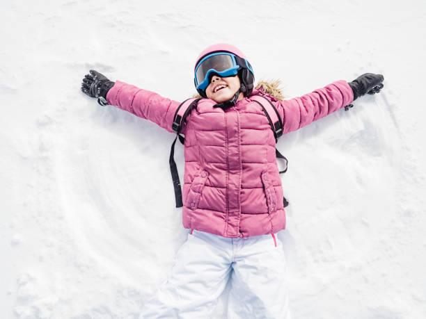 kleines mädchen lachten und spielten schnee-engel - gute winterjacken stock-fotos und bilder