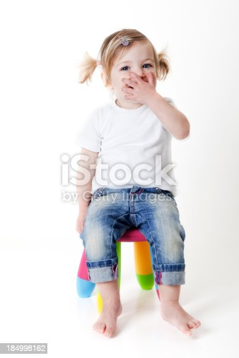little girl laughing with hand covering her mouth