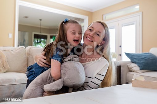 Cheerful mom embraces and tickles her little girl as they relax in their home.