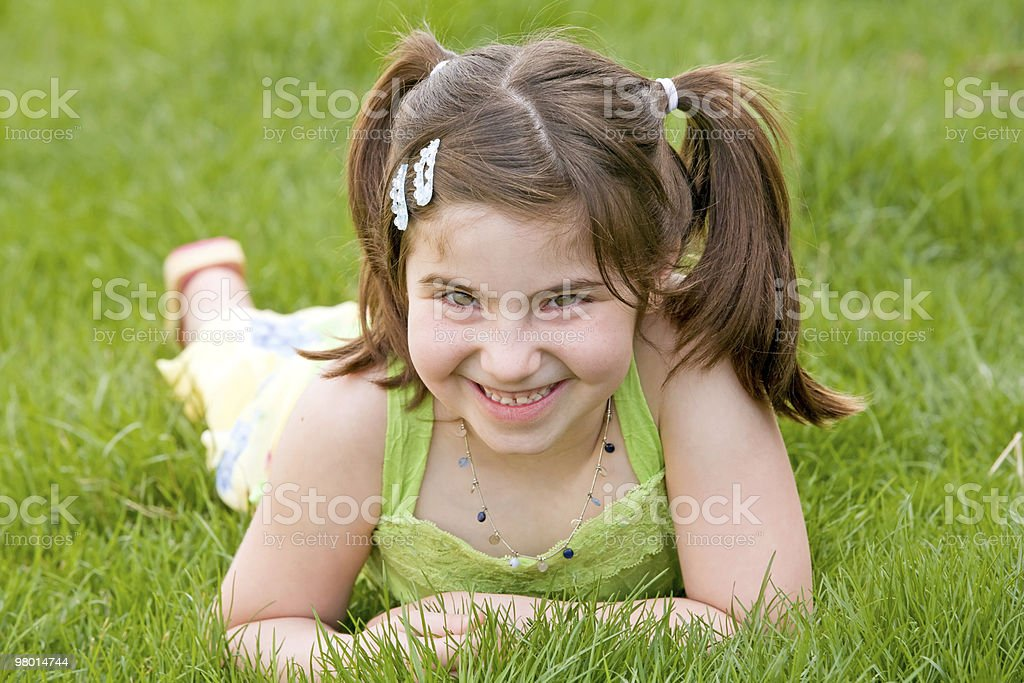 Little Girl Laying in the Grass Laughing royalty-free stock photo