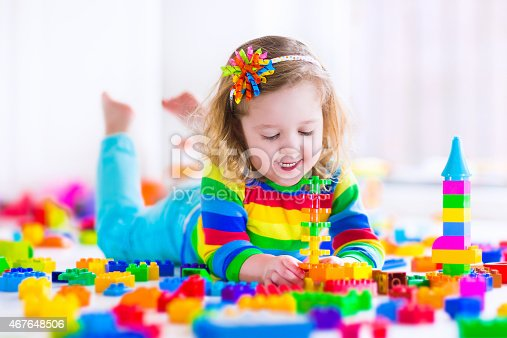 istock Little girl lays on stomach playing with rainbow toy blocks 467648506