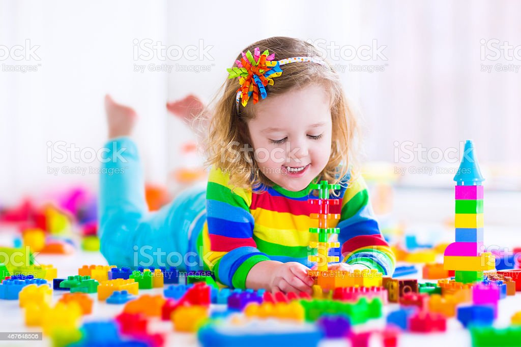 Little girl lays on stomach playing with rainbow toy blocks stock photo