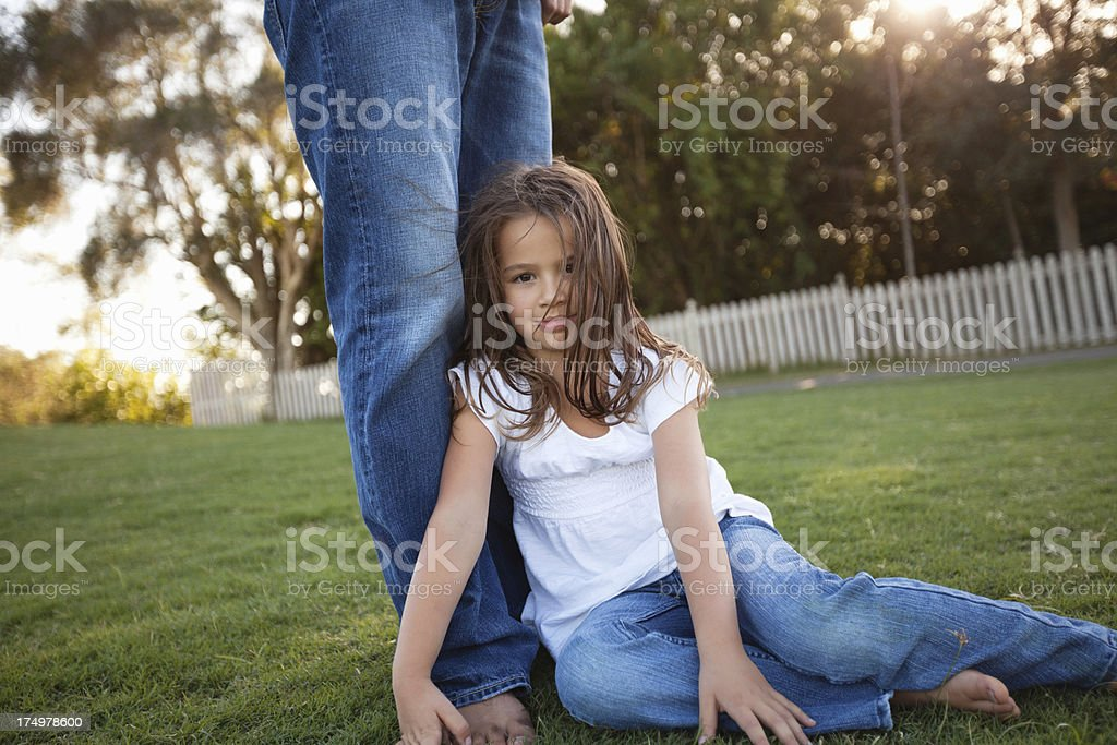 Little Girl Leaning Against Father's Legs At Park royalty-free stock photo