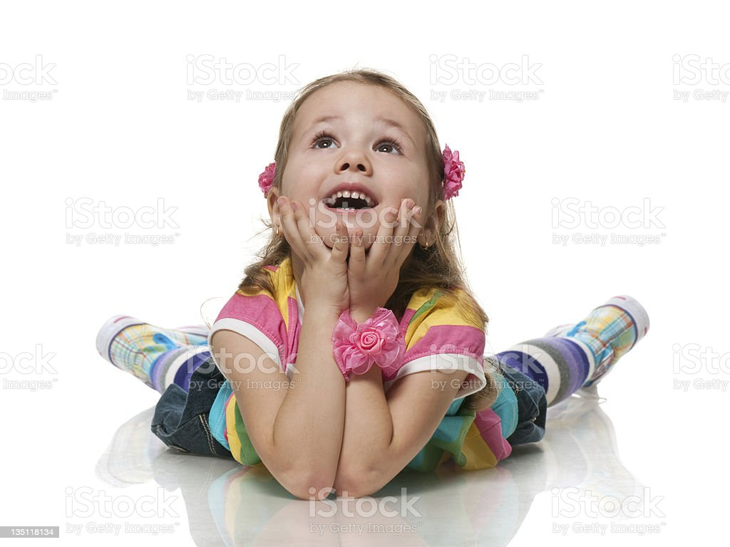Little girl leaning on her elbows looking up and smiling stock photo