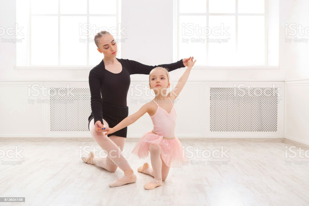 Little girl learn ballet with teacher copy space stock photo