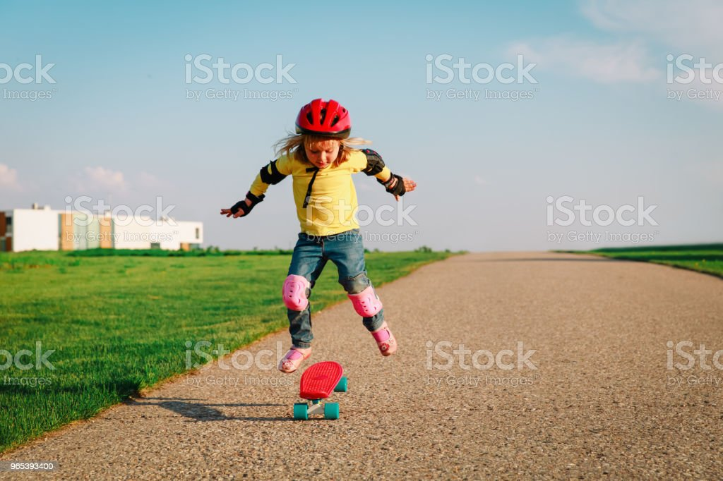 little girl learn to ride on skateboard outside zbiór zdjęć royalty-free