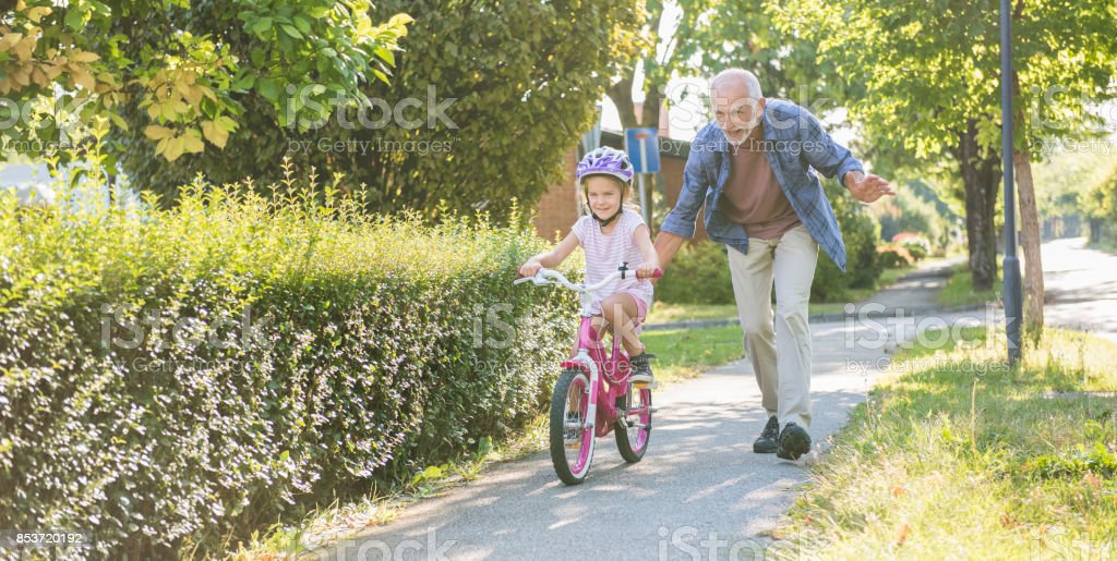 Little Girl Learning Ride A Bike With Grandfather stock photo