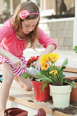 Subject: Happy little girl planting Gerber daisies in front of the house.