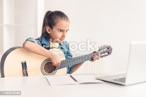 Focused little kid playing acoustic guitar and watching online course on laptop while practicing at home