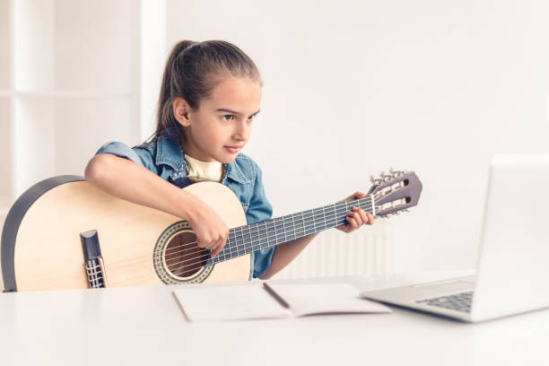 Little girl learning to play guitar online stock photo