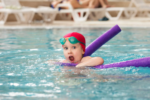 Little girl learning to swim in a pool stock photo