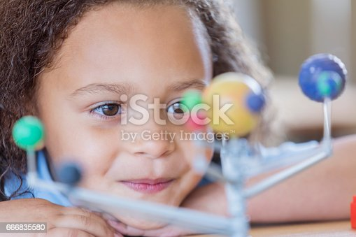 istock Little girl learns about the planets 666835580