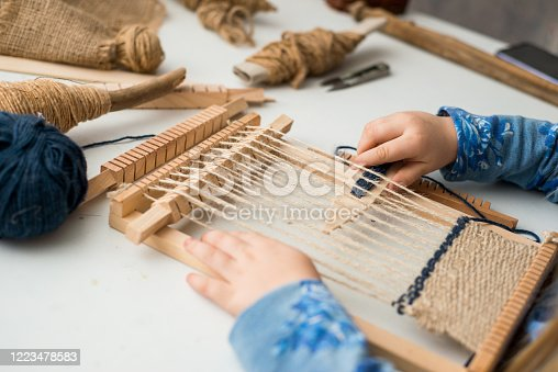 A little girl learns process to weave thick threads. Hands close up. Creating a picture by weaving.