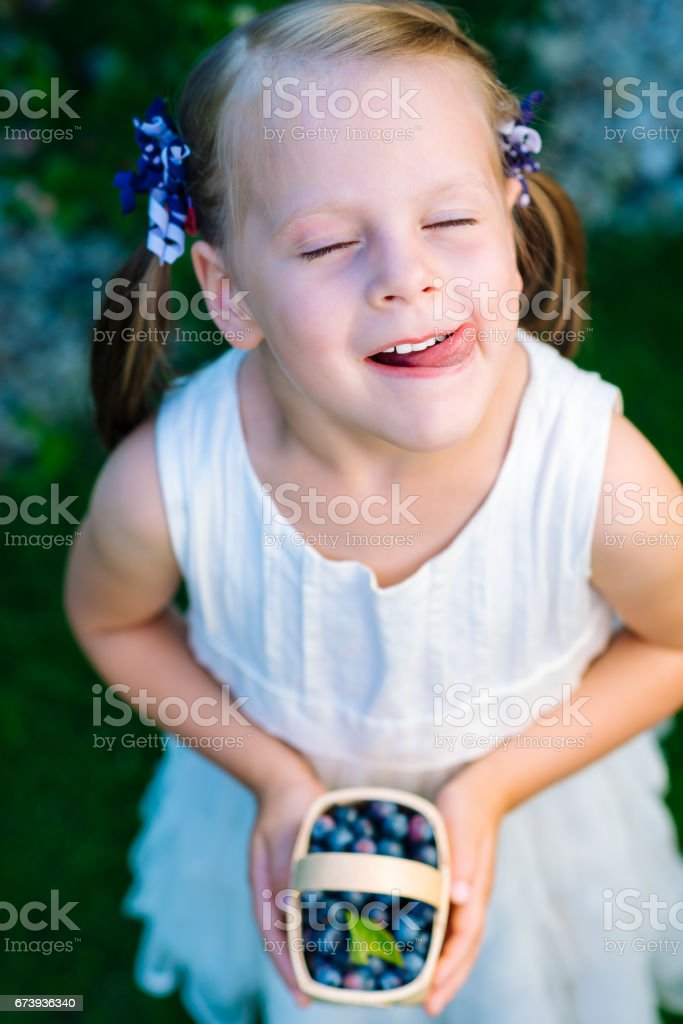 Little girl licking her lips with her eyes closed holding a basket of blueberries photo libre de droits