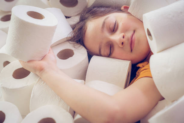 Little girl lies in toilet papers stock photo