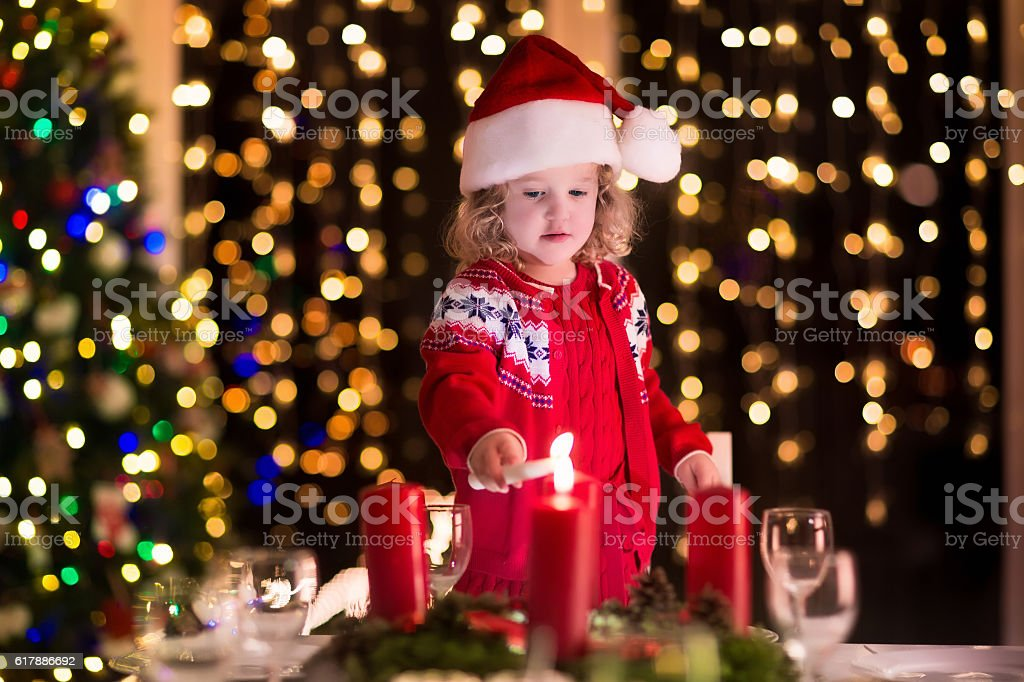 Little girl lighting candles at Christmas dinner on Xmas eve - foto de acervo