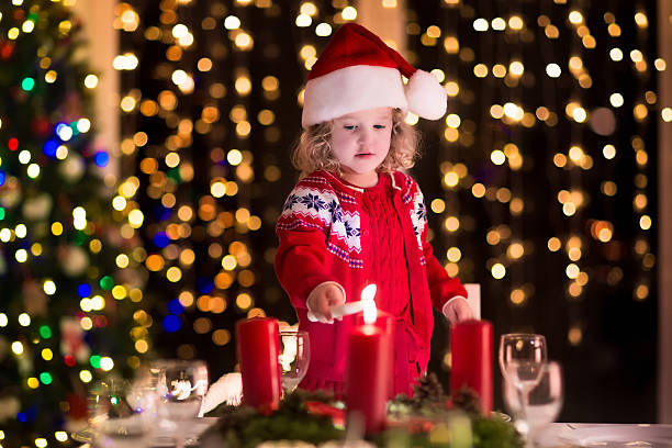 Little girl lighting candles at Christmas dinner on Xmas eve stock photo