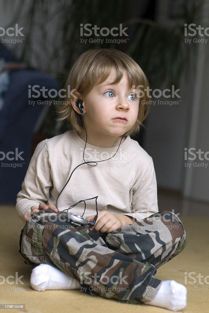 Little girl listening to bad music. stock photo