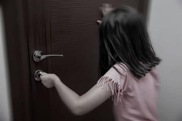 little girl locks the door stock photo